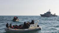 Des secouristes britanniques aident des migrants sur un bateau semi-rigide