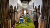 Une large pelouse verte synthétique et des clubs de golf accueillent les paroissiens.