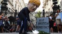 Un manifestant, portant un masque représentant Boris Johnson, proteste face à Downing Street à Londres, devant une fausse pierre tombale gravée des mots «RIP British Democracy», le 28 août dernier.