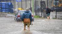Deux hommes dans l'eau d'une rue inondée le 14 juillet 2021 à Hagen, dans l'ouest de l'Allemagne, après que de fortes pluies ont frappé certaines parties du pays, provoquant des inondations généralisées.