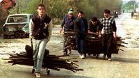 Un groupe de Bosniens transporte du bois pour se chauffer, le 27 octobre 1992 à Sarajevo [Patrick Baz / AFP/Archives]