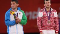 Les lutteurs ouzbek Soslan Tigiev (G) et russe Denis Tsargush (D) sur le podium des JO-2012 lors de la remise de leur médaille de bronze dans la catégorie des - de 74 kg, le 10 août 2012 à Londres [ / AFP]