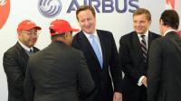 Le Premier ministre britannique David Cameron parle avec des responsables de la compagnie malaisienne AirAsia, le 13 novembre 2012 à Broughton, au nord-est du pays de Galles [Martin Rickett / Pool/AFP]