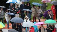 Des personnes regardent les stars monter les marches du Palais des festivals de Cannes sous des parapluies, le 18 mai 2013 [Loic Venance / AFP]