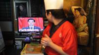 Un cuisinier regarde à la TV le discours du président chinois Hu Jintao, lors du 18e congrès du PCC, le 9 novembre 2012 à Shanghai [Peter Parks / AFP]