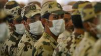 Des policiers saoudiens se protègent le visage avec un masque lors d'une épidémie de grippe aviaire en 2009 [Mahmud Hams / AFP/Archives]