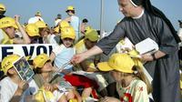 Une religieuse distribue des livres aux enfants, lors de la visite du pape Jean-Paul II à Osijekon, en Croatie, le 7 juin 2003 [Attila Kisbenedek / AFP/Archives]