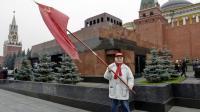 Un commuinste russe pose devant le mausolée de Lénine sur la Place Rouge à Moscou [Yuri Kadobnov / AFP/Archives]