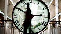 Une personne passe devant une horloge [Jeff Pachoud / AFP/Archives]