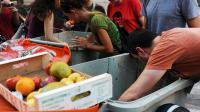 Des gens tentent de récupérer de la nourriture dans des poubelles [Dominique Faget / AFP/Archives]