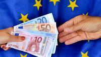 Echange de billets en euros sur fond de drapeau européen [Philippe Huguen / AFP/Archives]