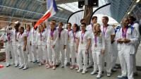La nageuse Camille Muffat avec le drapeau français accompagnée de l'équipe de France olympique à la gare St Pancras à Londres, le 13 août 2012. [Eric Feferberg / AFP/Archives]