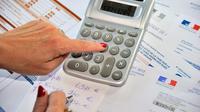 Une femme fait ses calculs pour remplir sa déclaration d'impôts, en septembre 2012 [Philippe Huguen / AFP/Archives]