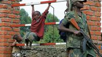 Des enfants jouent près d'un soldat rebelle du M23 le 7 mars 2013 à Bunagana [Isaac Kasamani / AFP/Archives]