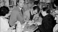Edouard Leclerc accueille les clients derrière le comptoir lors de l'inauguration du premier centre Leclerc ouvert en région parisienne, le 17 novembre 1959 à Issy-les-Moulineaux.