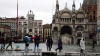 Les touristes s'adaptent à la montée des eaux grâce à des pontons installés place Saint Marc.