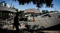 Un homme marche près d'un bâtiment effondré dans le village de Sugian sur l'île indonésienne de Lombok secouée par une série de séismes, le 20 août 2018 [str / AFP]