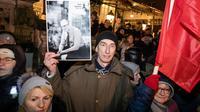 Un homme brandit une photo du maire de Gdansk lors des obsèques de Pawel Adamowicz, le 18 janvier 2019 à Gdansk [Wojtek RADWANSKI / AFP]