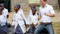 Le prince Harry esquisse quelques pas d'une danse traditionnelle avec des enfants au centre de Kananelo au Lesotho, le 27 février 2013 [Chris Jackson / Getty Images/AFP]