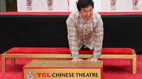 Jackie Chan pose ses empreintes dans le ciment du Chinese Theatre à Hollywood, le 6 juin 2013 [Frederick M. Brown / Getty Images/AFP]