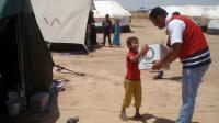 Un volontaire du Croissant Rouge irakien donne un kit humanitaire à un garçon déplacé à Khanaqin près de la frontière avec l'Iran, le 13 juillet 2014 [Younis al-Bayati / AFP/Archives]