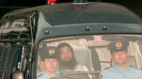 Sur cette photo du 19 juillet 1995, Shoko Asahara, gourou de la secte Aum, est conduit par la police à un tribunal de Tokyo [JIJI PRESS / JIJI PRESS/AFP/Archives]