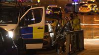 Des spectateurs près d'une salle de concerts à Manchester le 23 mai 2017, où une possible attaque terroriste a fait 19 morts et une cinquantaine de blessés [Paul ELLIS / AFP]