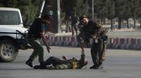 Les forces de l'ordre aident un de leurs collègues blessés après l'attentat suicide du 22 juillet 2018 à Kaboul [NOORULLAH SHIRZADA / AFP]