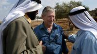 L'écrivain israélien Amos Oz discute avec des Palestiniens après la récolte d'olives à Aqraba, en Cisjordanie, le 30 octobre 2002. [Menahem KAHANA / AFP/Archives]