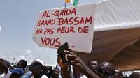 """Des Ivoriens portent une pancarte """"Al-Qaïda, Grand-Bassam n'a pas peur de toi"""", lors d'un hommage aux victimes de l'attaque jihadistes du 13 mars 2016 qui a fait 19 morts, le 20 mars 2016 à Grand-Bassam en Côte d'Ivoire [SIA-KAMBOU / AFP/Archives]"""