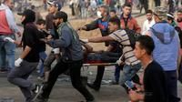 Un manifestant palestinien évacué après avoir été blessé lors de heurts avec les forces de sécurité israéliennes à la frontière entre la bande de Gaza et Israël, le 13 avril 2018  [MAHMUD HAMS / AFP]