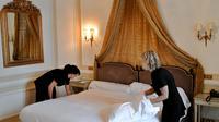 Deux femmes de chambre refont un lit dans un hôtel [Franck Fife / AFP/Archives]