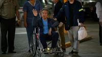 L'ancien président péruvien (1990-2000) Alberto Fujimori salue ses supporteurs alors qu'il est escorté hors de la clinique Centenario par son fils, le député Kenji Fujimori, à Lima, le 04 janvier 2018 [LUKA GONZALES / AFP]