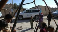 Des enfants dans les rues de la ville d'Utaya, dans l'enclave syrienne de la Ghouta Orientale, tandis qu'un convoi d'aide humanitaire pénètre dans la ville le 14 février 2018 [ABDULMONAM EASSA / AFP]