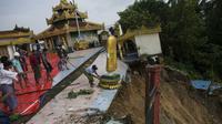 Des ouvriers déplacent une statue de Bouddha de la pagode Kyeik Than Lan, dans le sud de la Birmanie, endommagée par un glissement de terrain, le 18 juin 2018 [Ye Aung THU / AFP]