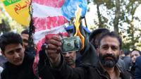 Un Iranien brûle un dollar lors d'une manifestation le 4 novembre 2018 à Téhéran marquant le 39e anniversaire de l'occupation de l'ambassade américaine [ATTA KENARE / AFP]