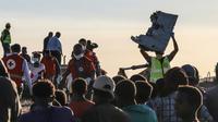 Un homme porte un débris d'avion sur le site du crash du Boeing 787 d'Ethiopian Airlines, près de Bishoftu, à 60 km d'Addis Abeba, le 10 mars 2019 [Michael TEWELDE / AFP]
