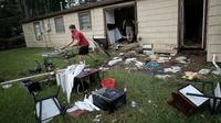 Chris Gaspard sort des meubles abimés par les inondations de la maison de son ami Bryan Parson le 1er spetmbre 2017 à Dickinson, Texas [WIN MCNAMEE / GETTY IMAGES NORTH AMERICA/AFP]