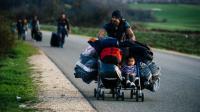 Un homme transporte dans une poussette son fils et des affaires personnelles sur une route près de la frontière entre la Grèce et la Macédoine, le 8 mars 2016 [DIMITAR DILKOFF / AFP]