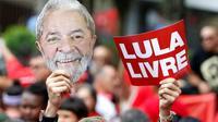 """Un partisan de Lula brandit un masque représentant le visage de l'ancien président brésilien et une pancarte """"Lula libre"""" au lendemain de sa libération, lors d'un rassemblement devant le siège des métallos de Sao Bernardo do Campo, près de Sao Paulo, le 9 novembre 2019 [Miguel SCHINCARIOL / AFP]"""