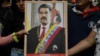 Des partisans du président vénézuélien Nicolas Maduro exhibent son portrait à Caracas, le 7 janvier 2019.  [YURI CORTEZ / AFP]