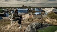 """Un homme appelle sa famille restée au Soudan le 5 novembre 2015 dans """"la Jungle"""" à Calais [PHILIPPE HUGUEN / AFP/Archives]"""