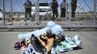 Des chaussures d'enfants disposées devant le poste-frontière de Tornillo près d'El Paso, aux Etats-Unis, lors d'un rassemblement contre les séparations de familles de migrants, le 21 juin 2018 [Brendan Smialowski / AFP]