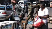 Deux soldats zimbabwéens cagoulés crient des ordres à des vendeurs de rue et des changeurs de billets, lors d'une patrouille dans les rues de Harare, le 2 août 2018 [MARCO LONGARI                                                                                                                                                                                                                                                   / AFP]