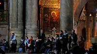 Des fidèles prient dans l'église de Saint-Sépulcre, à Jérusalem, rouverte le 28 février 2018 après trois jours de fermeture [THOMAS COEX / AFP]