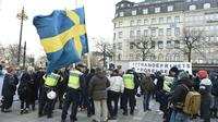 Des policiers suédois s'adressent à des manifestants, le 30 janvier 2016 à Stockholm qui s'opposent à l'arrivée de migrants dans leur pays [Marcus Ericsson/TT / TT NEWS AGENCY/AFP]