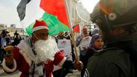 Un manifestant palestinien habillé en père Noël s'oppose à un membre des forces de l'ordre israélienne à Bethléem, en Cisjordanie occupée, le 23 décembre 2017 [Musa AL SHAER / AFP]