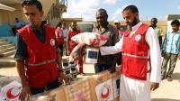 Des membres du Croissant Rouge lybien distribuent de l'aide aux migrants détenus à Tulmitha, à 100 km à l'est de Benghazi, le 16 août 2016 [Abdullah DOMA / AFP/Archives]