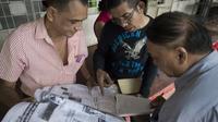 Les partisans d'Aung San Suu Kyi consultent les résultats des élections dans un quotidien le 10 novembre 2015 à Rangoun [NICOLAS ASFOURI / AFP]