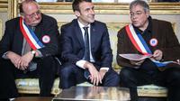 Emmanuel Macron avec Vanik Berberian (D), président de l'Association des maires ruraux de France et le secrétaire général Michel Fournier (G), le 14 janvier 2019 à Paris [Ludovic MARIN / POOL/AFP]